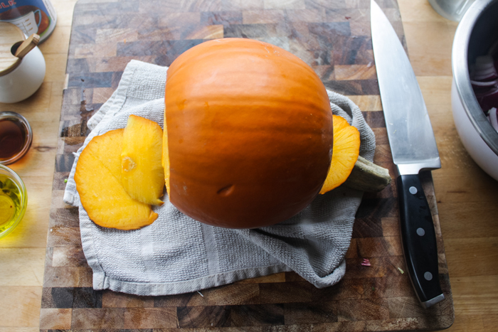 Cutting a pumpkin can be very dangerous, so make sure there are no slippery surfaces and be confident with your sharp knife.   Put a clean dish towel underneath the pumpkin to keep it from moving, and with a back and forth motion, cut off the top and bottom of the pumpkin.