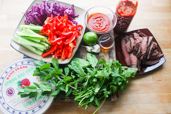 The ingredients: Grilled london broil, rice paper, cucumber, purple cabbage, red bell pepper, mint, sweet basil, cilantro. And for the sauce, Sriracha, fish sauce, lime, and garlic cloves