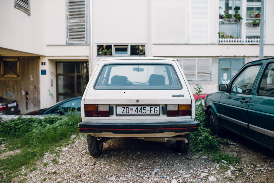 An old Yugoslav hatchback parked in front of one of the lackluster concrete apartment buildings in the city center.