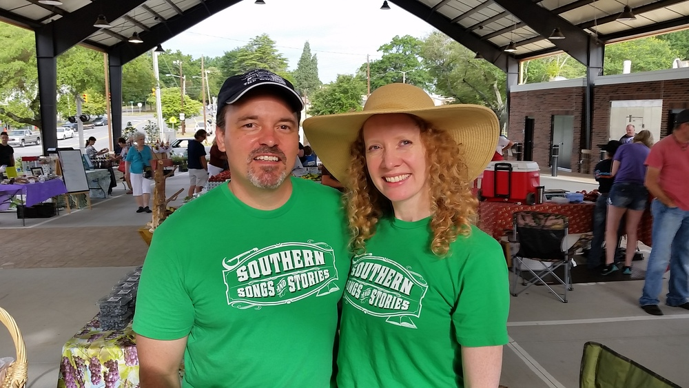 Joe and Amy Kendrick wearing their Southern Songs and Stories t-shirts at the Shelby, NC farmers market