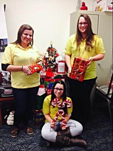 Carlie Barella, Kara Sage, Hannanel Sage (seated) wrapped presents for elderly clients of Home Instead Senior Care.