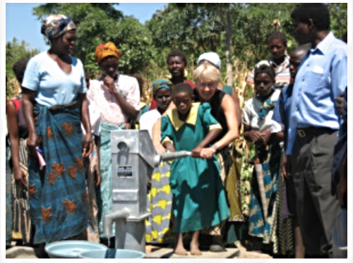 KAREN IN MALAWI, TEACHING A CHILD HOW TO PUMP THE WELL (COURTESY: DRILLING FOR HOPE)
