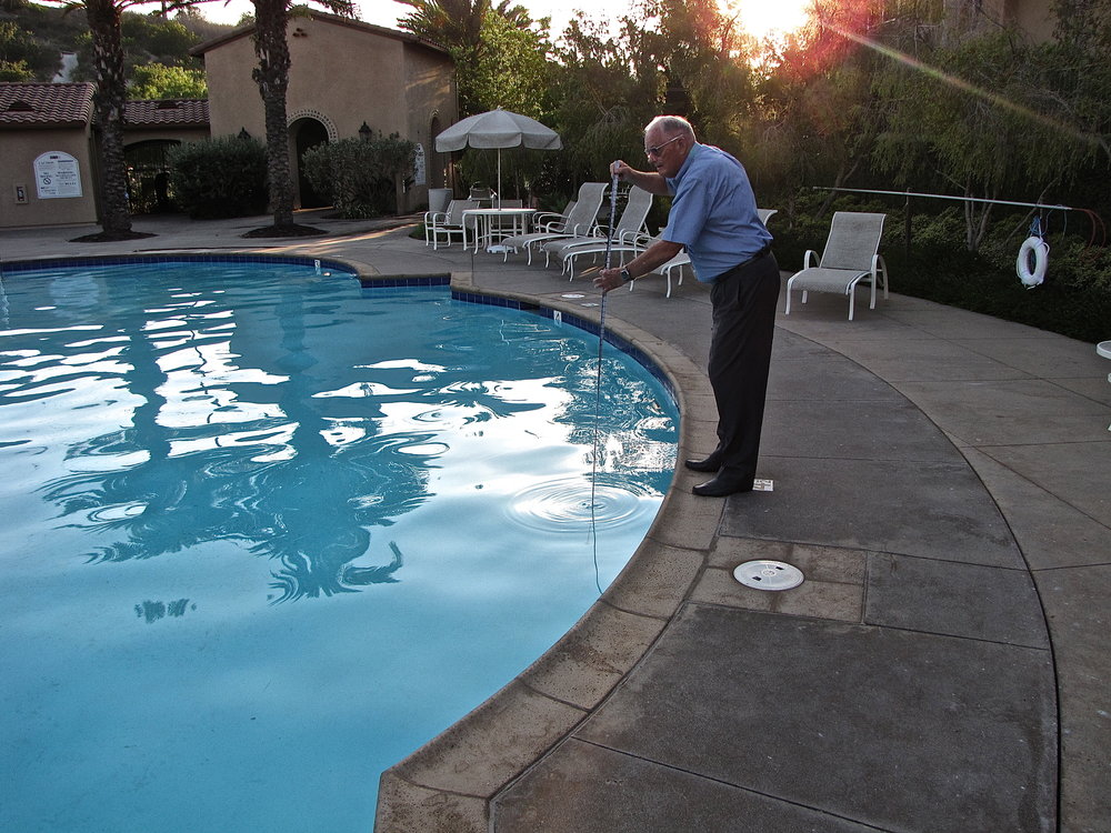 Photo of Dr. Rowley taking a depth measurement near a swimming pool depth marker.