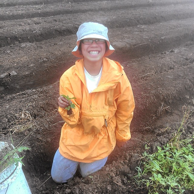 Madeline braves the rain to pick weeds with everyone else and it looks like she's enjoying herself!