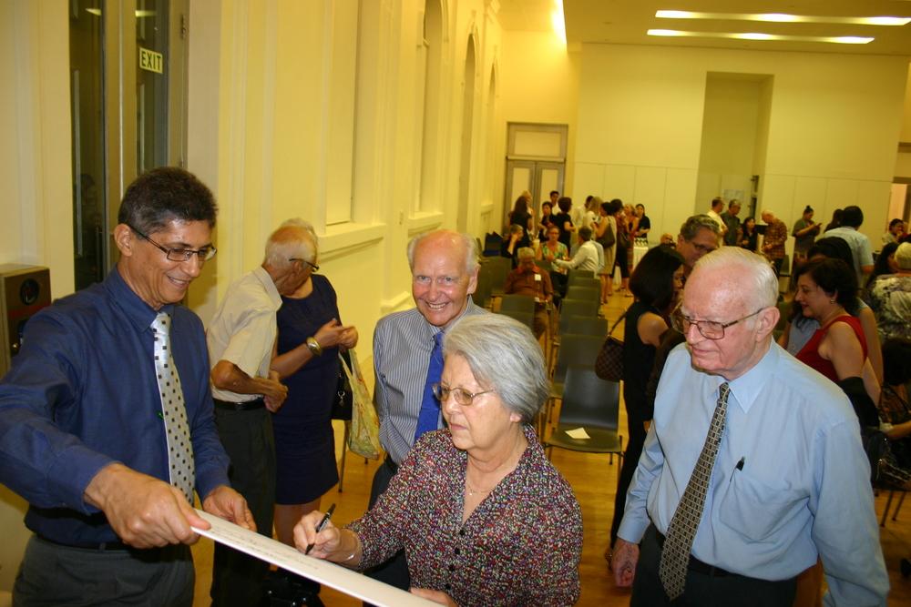 Claire Edwards (nee de Souza) ex-settler signing the guest register
