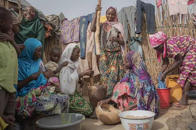 """""""At least we are here together."""" Ladi (far right) says of being displaced to a camp on the outskirts of Maiduguri after Boko Haram attacked her village and killed her husband. She is pictured here with her adult daughters. Laughter was the chorus to a long morning of chores in the hot sun.  April 2018 (c) Emily Kinskey / Malteser International"""