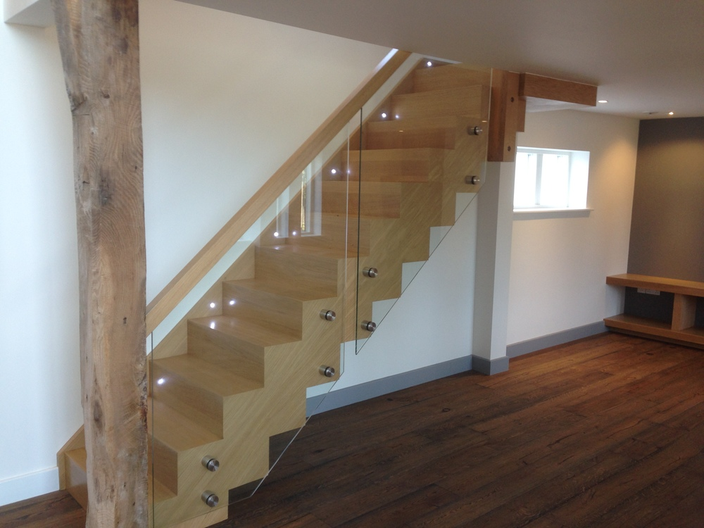 A sleek timber staircase with glazed balustrade cantilevers off the side wall, enhancing the open plan feel of the property. The Clients specified a sleek modernfeel to the interior,although some key existing timbers were retained and exposed, retaining elements exploringthe history of the building.  Bespoke Oak Staircase:  Weybread Woodcraft, Fressingfield