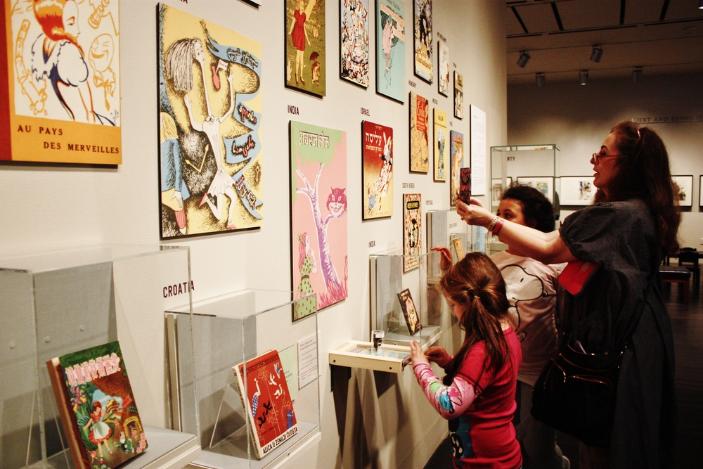 "A woman and two children gaze at illustrated book covers of ""Alice's Adventure in Wonderland"" from various countries."
