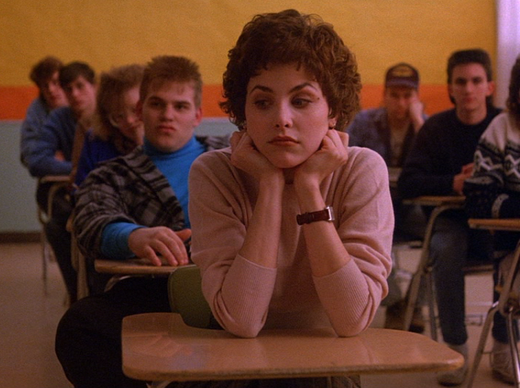"""AUDREY HORNE    From the pilot episode of """"  Twin Peaks  ,"""" Audrey Horne's outfits struck a balance between innocent and seductive. She often combines prim school-girl style clothing with more mature pieces that give viewers a glimpse of the independent woman hiding behind her daddy's-girl facade. Audrey's iconic pink sweater not only fits beautifully and shows off her figure, but allows her to hide behind the innocence of the pastel hue. To channel Audrey this autumn, cop a similar sweater from    American Apparel."""