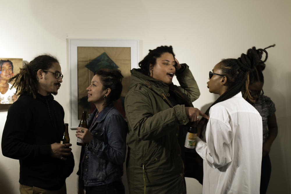 Graduate student X'ene Sky Taylor (far right) near drawings of Michael Brown and Aiyana Jones.