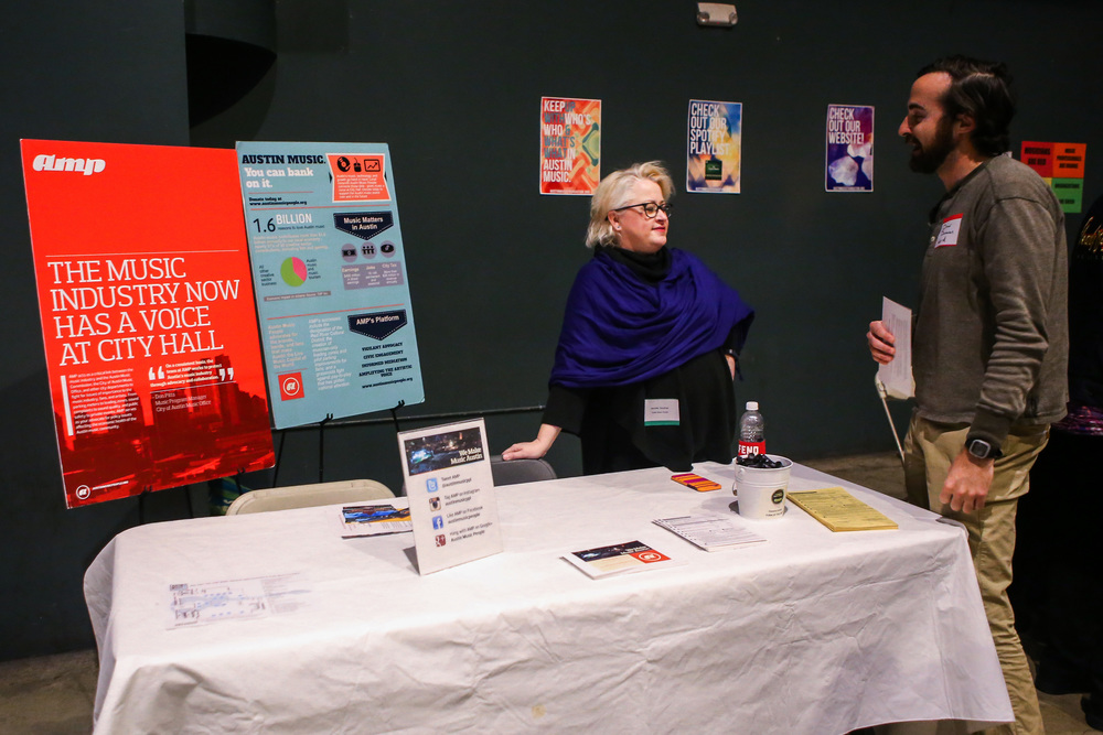 """A representative from Amp talks with a local musician at Austin Music Foundation's """"Feel the Love"""" Expo on Feb. 10, 2016."""