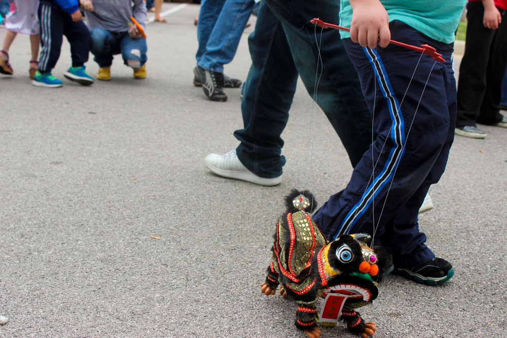 A little boy walks a Chinese dragon puppet alongside him throughout the festival.