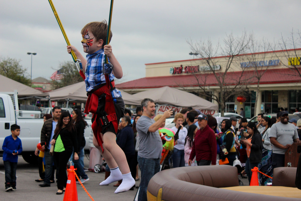 A face-painted boy bounces over the crowd's heads.