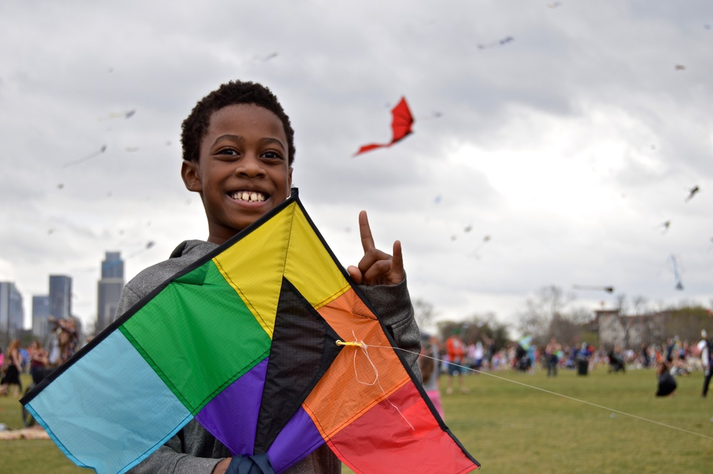 A young boy shows UT school spirit with his rainbow colored kite.