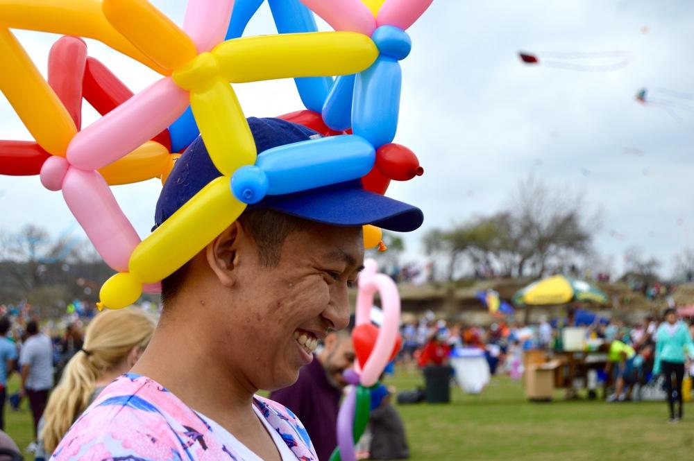 A festival volunteer makes balloon animals for children.