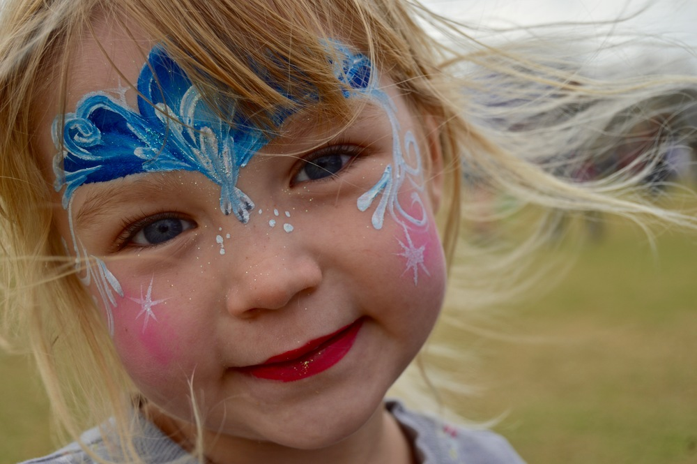 """This young girl just got her face painted and insisted on taking a picture of her """"princess moment."""""""