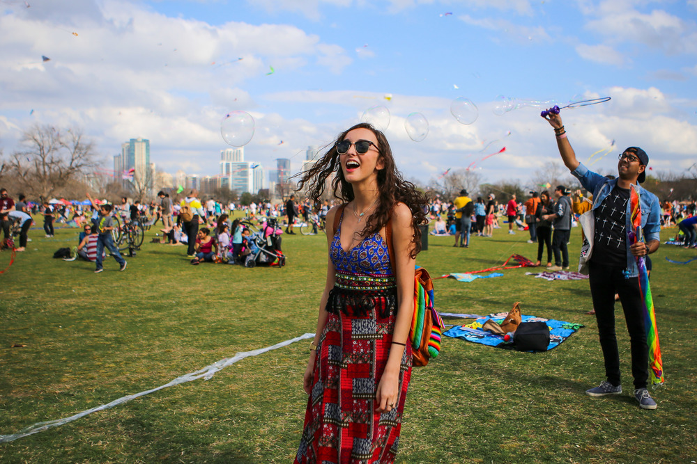 Senior Ashlyn Simon laughs as an attendee waves bubbles into the air. Simon says this was her first Kite Festival at Zilker park.