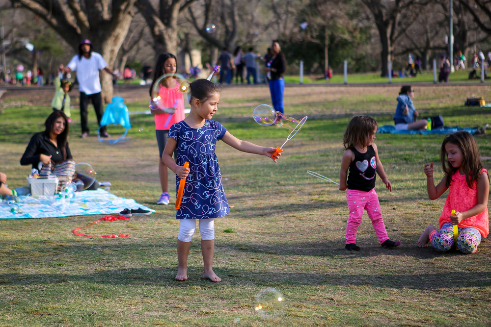 Families and children enjoy the excellent weather at Zilker Park. A girl takes a break from flying a kite to blow some bubbles.