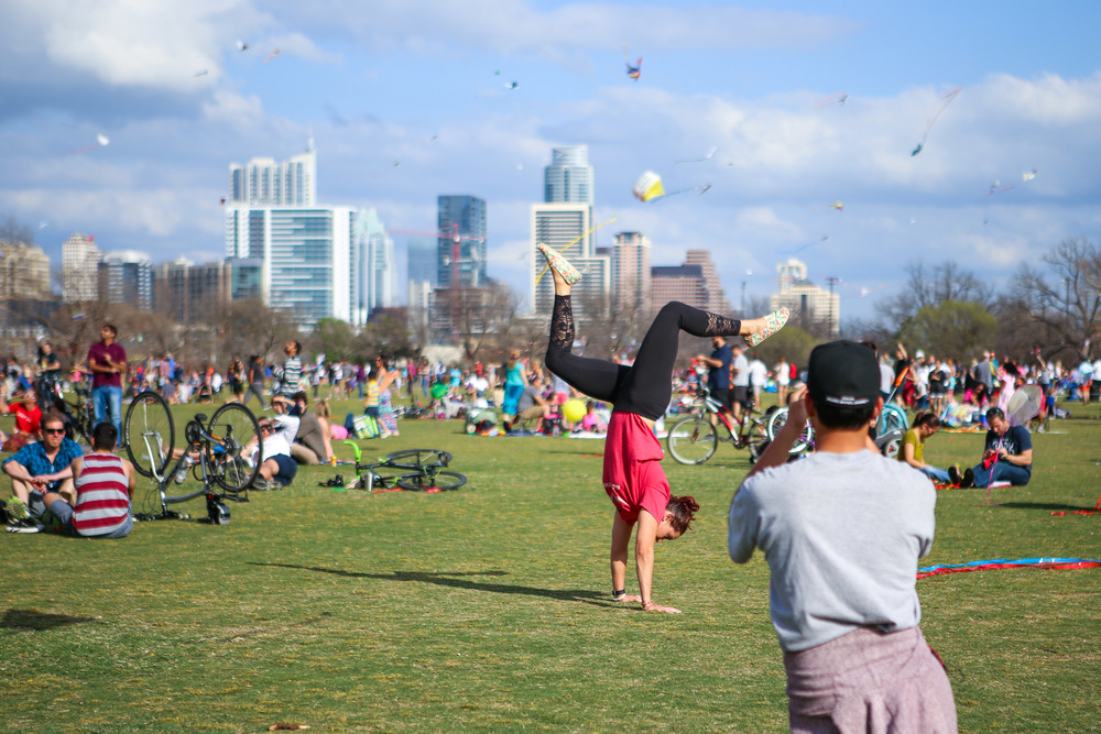 The Austin skyline was filled with colorful kites, making an idyllic background for this woman's pose.