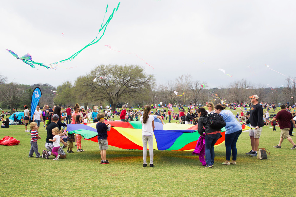 People bounce a ball on a colorful parachute while kites soar overhead.