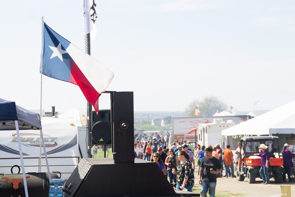 The Texas flag waves as crowds gather, tasting samples from competing barbecuers at BBQ Austin.