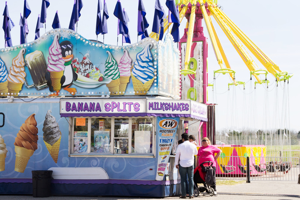 A dessert stand advertises banana splits, milkshakes, and even frozen chocolate-dipped cheesecake, drawing a crowd in the hot sun.