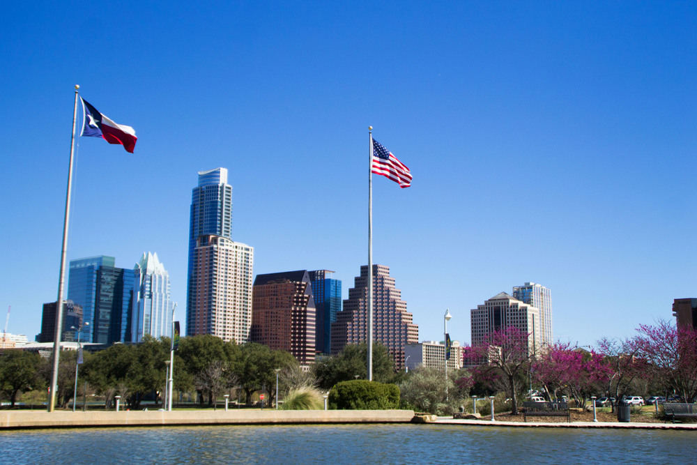 The warm spring wind blows as the Texas and United States flags frame the downtown Austin skyline, as seen from the Long Center.