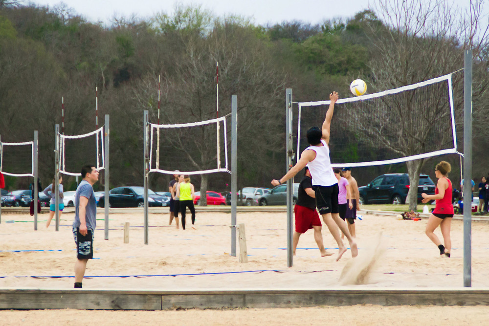 A man jumps up to hit a volleyball during a casual game at Zilker Park.