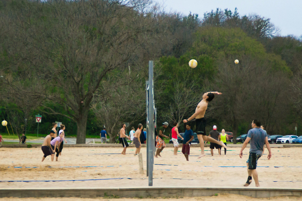 Spring weather brings spring sports— a group of athletes play sand volleyball at Zilker Park.