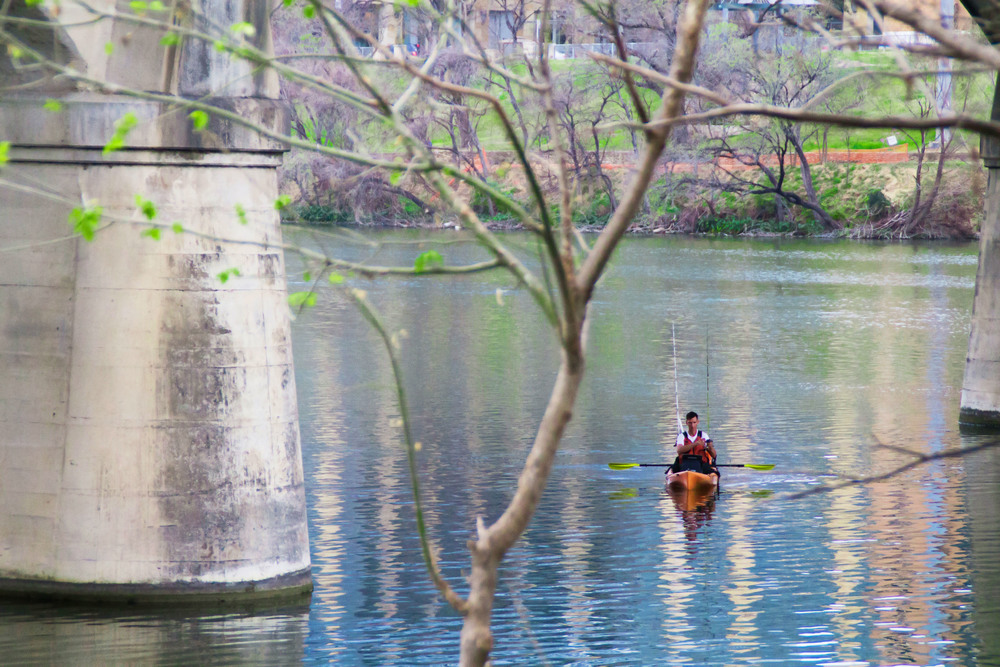 Town lake reflects the vibrant colors of spring time as a kayaker floats, taking advantage of the warm weather.