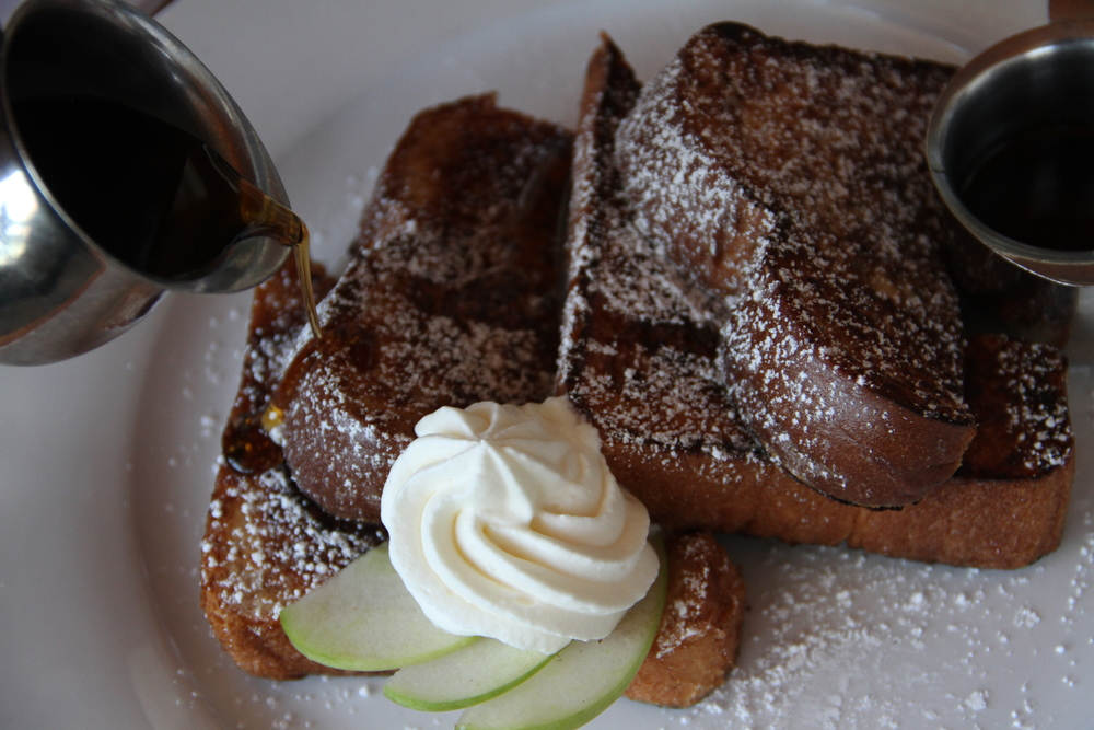 Olivia's brioche french toast topped with mandolin-sliced apples, whipped cream and drizzled with vanilla syrup.