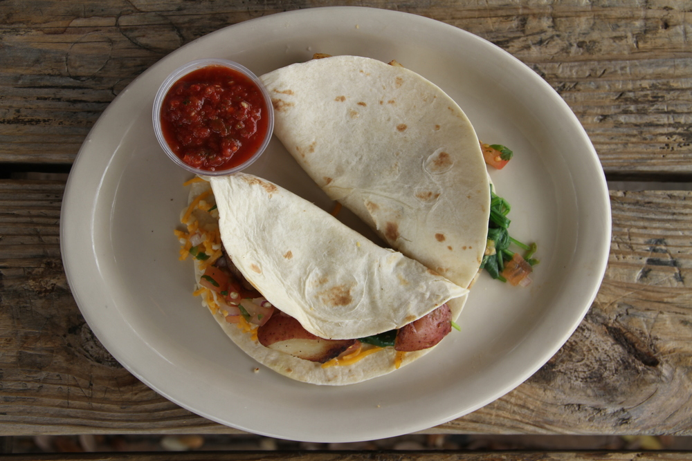Garden breakfast tacos filled with red potatoes, steamed spinach, pico de gallo and a cheddar and jack cheese blend. Accompanied with salsa and a picnic table with lovers' initials engraved in its wood.