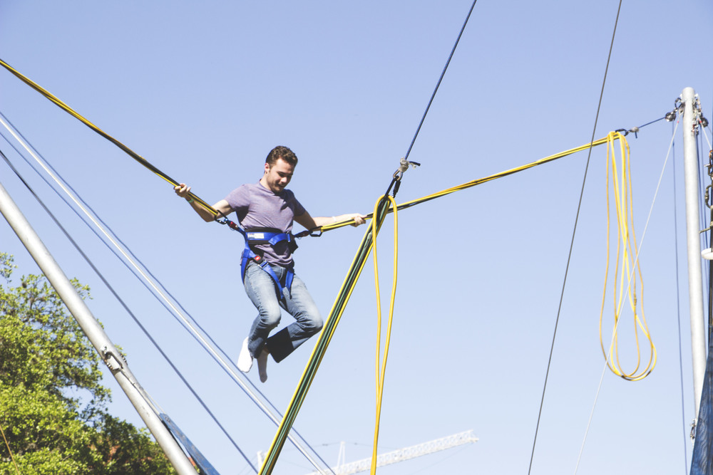 A festival attendee bungee jumps.