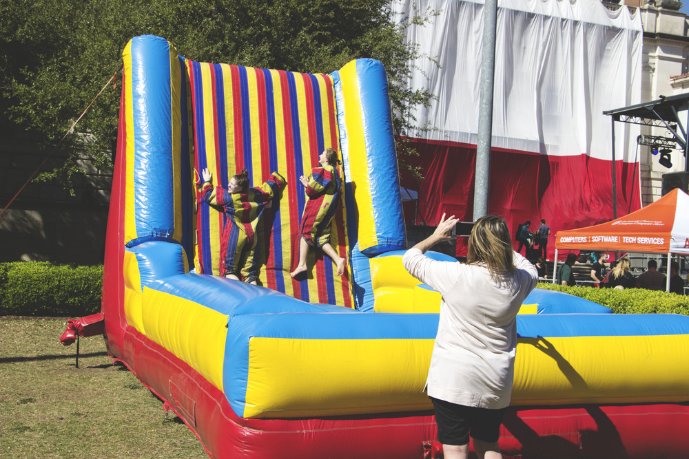 Two UT visitors play at the velcro wall, as their mom takes their photograph.