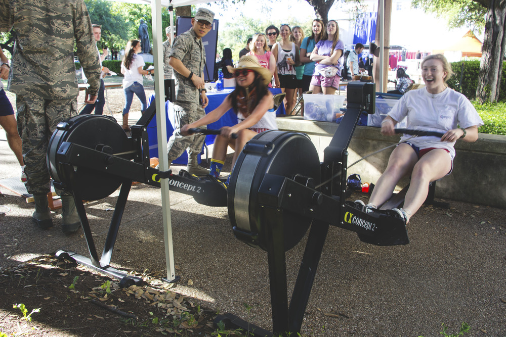 Two attendees compete with one another to get the best 'rowing' time.