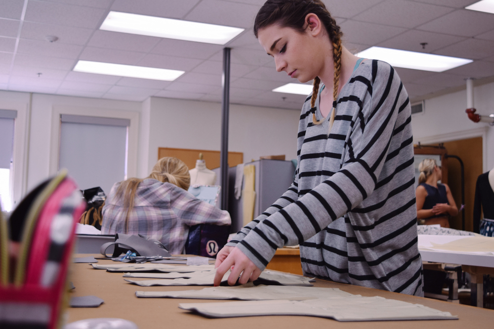 Kristen arranges fabric to start piecing together her next garment.