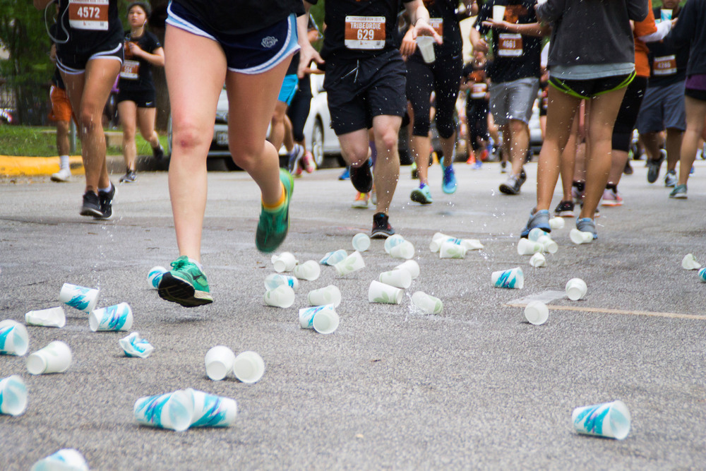 Splashing around runners' ankles, used water cups crash to the ground at a water station on Whitis Avenue.
