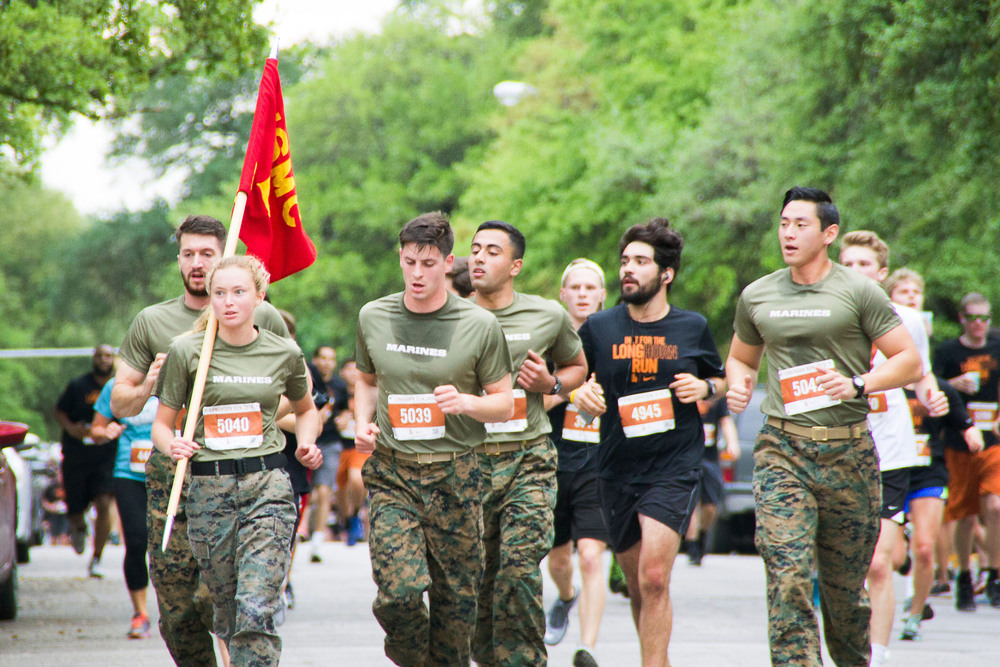 Members of the US Marine Corps run in their uniforms at the last leg of the race, displaying pride for their country.