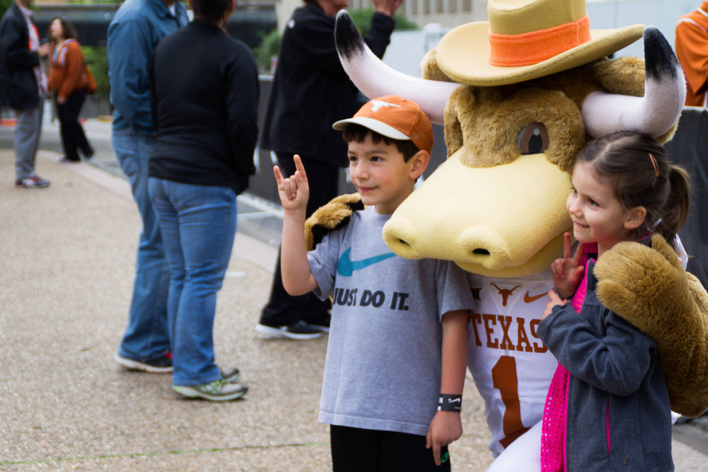 Little longhorns get a bear-hug from Bevo at the sideline of the starting line.