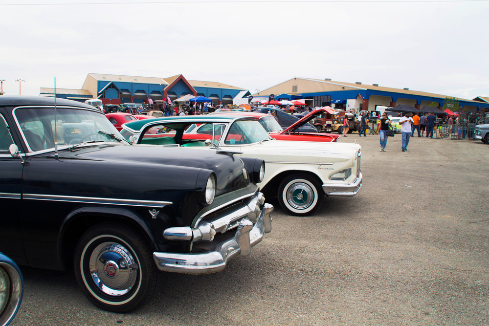 Spectators mill around in the background of the Lonestar Round Up, glossy cars lined up in a row with care.