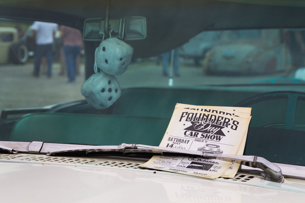 Advertisements for another upcoming car show are fastened under the windshield wipers of a display car, trademark fluffy dice dangling from the rearview mirror.