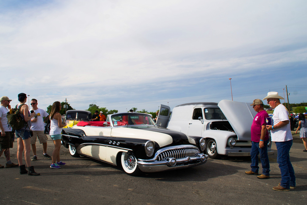 People stand around, scrutinizing a glossy black and white vehicle. People of all ages joined together to enjoy the wide variety of cars present.