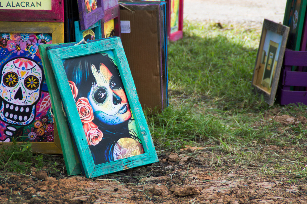 A beautiful painting with a rustic frame leans against a stand amongst other paintings. Many artists took advantage of the Lonestar crowds to promote and sell their works.