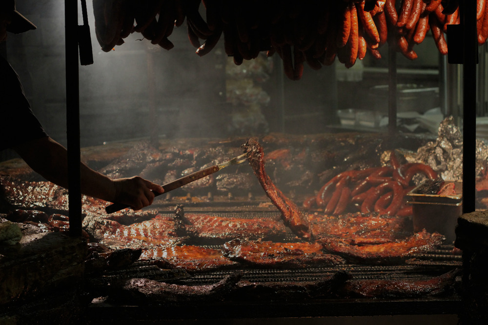 Barbecue masters at Salt Lick spend their Saturday afternoon hovering over their open barbecue pit, tending to the sea of meats to be served to hungry lunch-goers.    Photo by Jamie Medina