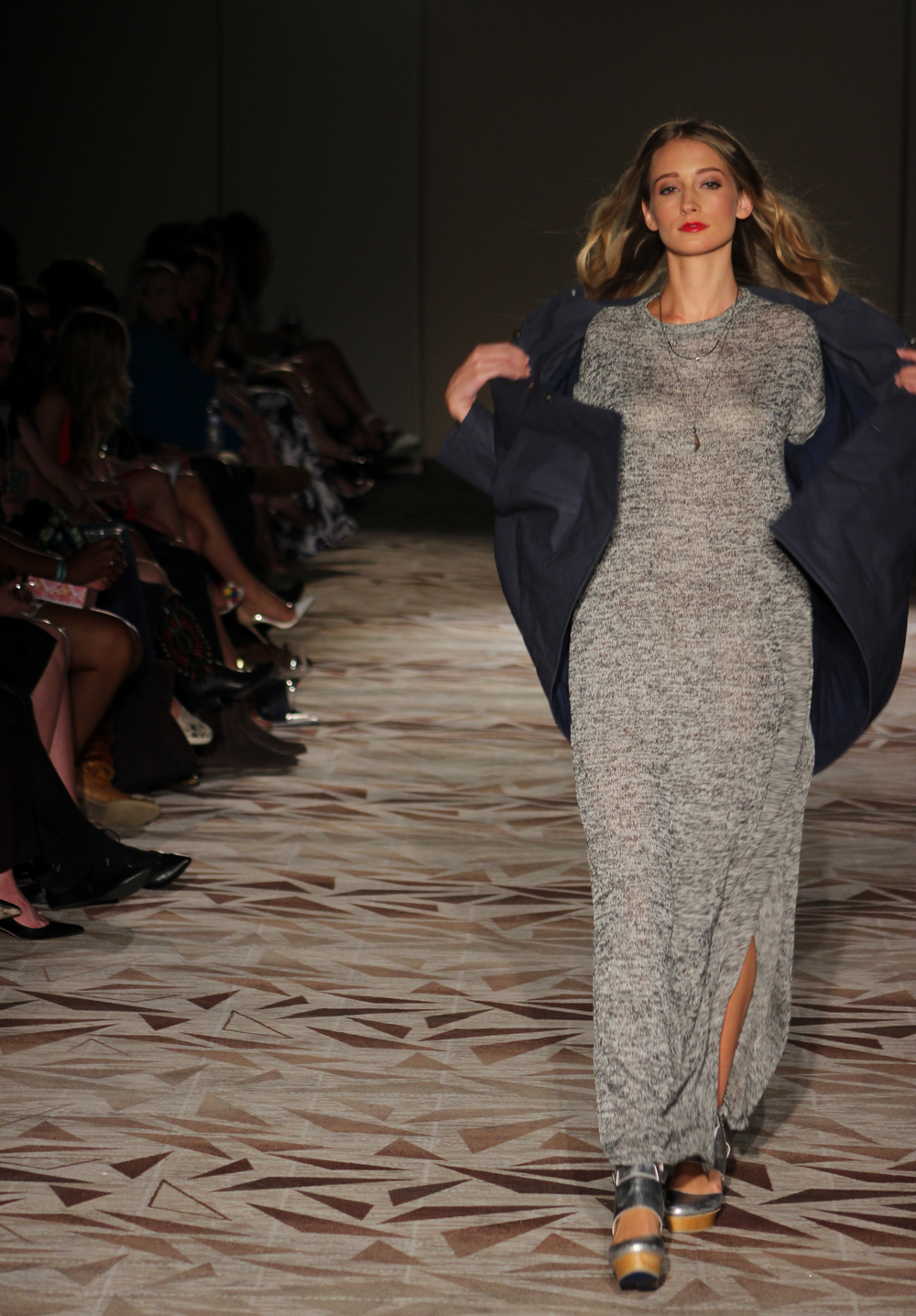 A model struts down the runway and shows off a grey knit dress from M.E. Shirley's collection. Photo by Miranda Chiechi.