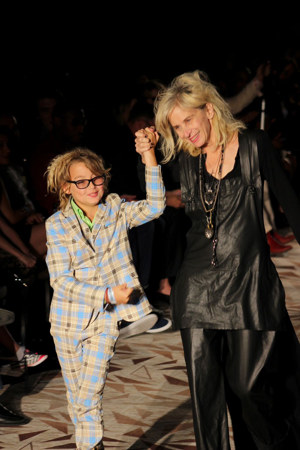 Gail Chovan smiles with her son as she walks down the runway after showing her collection. Photo by Miranda Chiechi.
