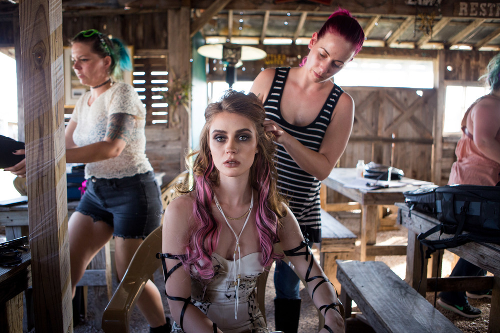Hair stylist Michi Lafary adjusts model Anna Cash's hair for the first look of the shoot on site in Manor, Texas.