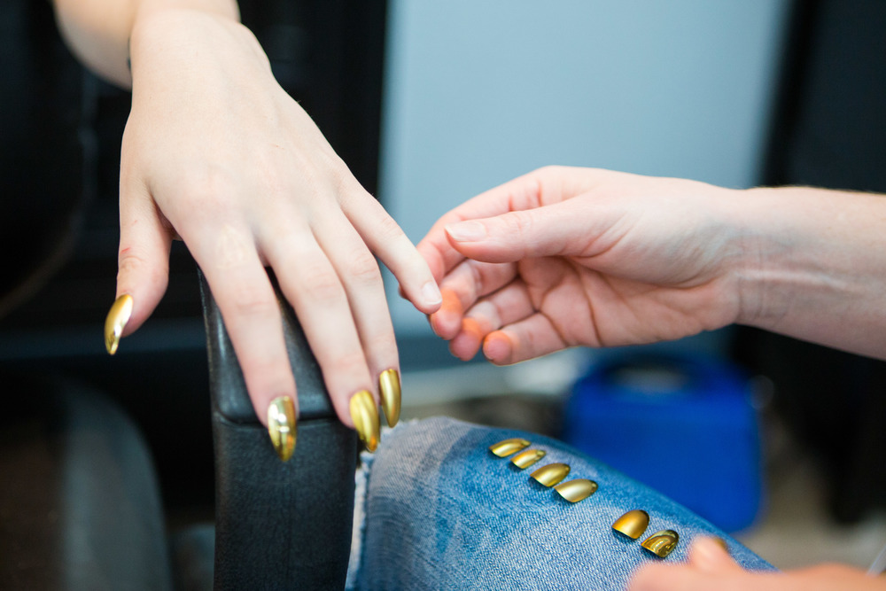 Makeup artist and nail technician Lauren Garcia apply fake golden nails to model Anna Cash in preparation for the shoot.