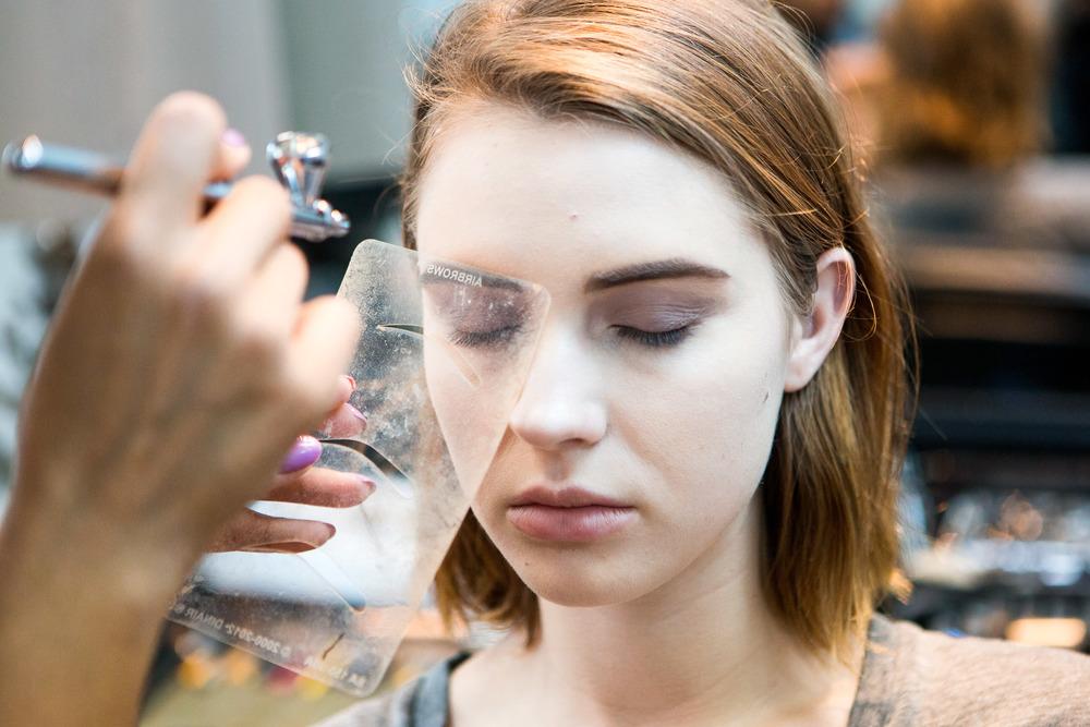 Makeup artist Lauren Garcia applies makeup to model Anna Cash with her airbrush makeup gun.