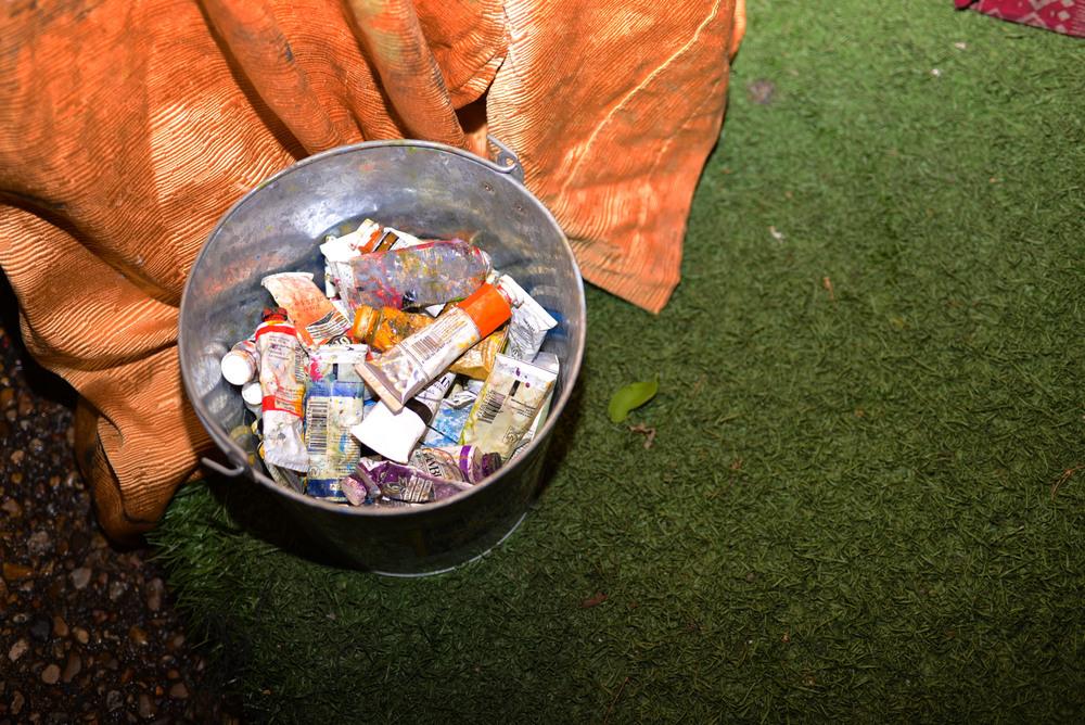 A bucket of paint serves as an artist's right hand at Empire's backyard art show. Photo by Dahlia Dandashi.
